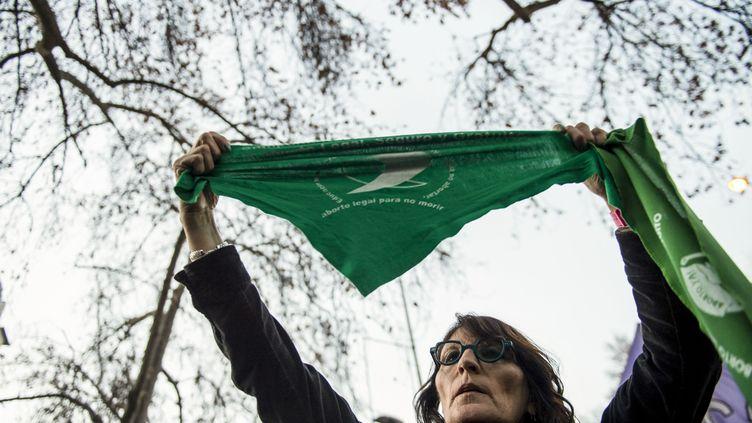 Une femme manifestant pour le droit à l'avortement en Argentine porte un foulard vert, symbole de la lutte pour ce droit, lors d'un rassemblement devant l'ambassade de l'Argentine au Chili, le 8 août 2018. (MARTIN BERNETTI / AFP)