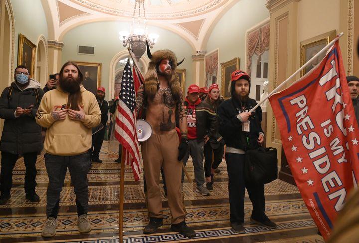 """Jacob Anthony Chansley, le """"chaman QAnon"""" (au centre), lors de l'envahissement du Capitole par des partisans de Donald Trump à Washington (Etats-Unis), le 6 janvier 2021. (SAUL LOEB / AFP)"""
