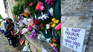 Fleurs et pancartes déposées devant le domicile de Sandra P. lors d'un hommage à la jeune femme à Bordeaux le 4 juillet 2021. (MEHDI FEDOUACH / AFP)