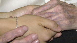 Les mains d'une personne agée et d'une jeune personne. Photo d'illustration. (MEHDI FEDOUACH / AFP)