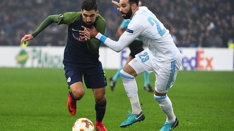 Adil Rami (Marseille) aux prises avec Munas Dabbur (Salzbourg) (ANNE-CHRISTINE POUJOULAT / AFP)