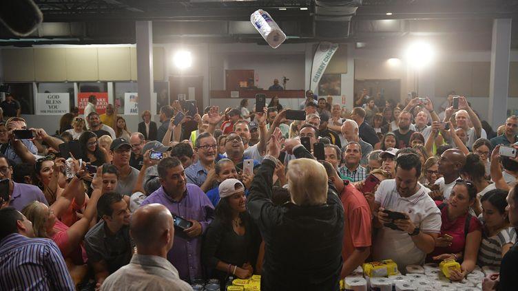 Le président américain, Donald Trump, lance des rouleaux d'essuie-tout dans l'assistance, à Porto Rico, le 3 octobre 2017. (MANDEL NGAN / AFP)