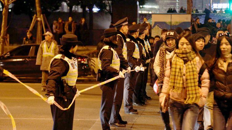 Des policiers chinois encadrent les passants à Shanghai (Chine), le 1er janvier 2015. (IMAGINECHINA / AFP)