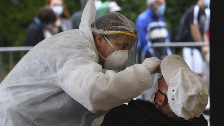 Unsoignant réalise un test de dépistage du coronavirus Covid-19 à Quiberondans le Morbihan, le 27 juillet 2020 (photo d'illustration). (FRED TANNEAU / AFP)