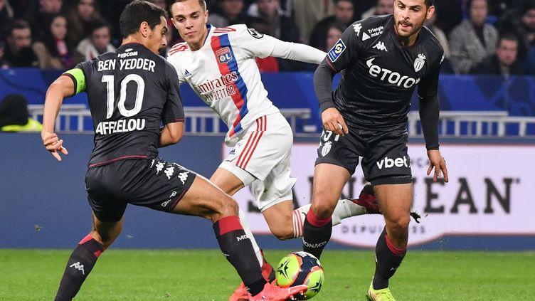 Le Lyonnais Maxence Caqueret cerné par les Monégasques Wissam Ben Yedderet Kevin Volland, le 16 octobre au Groupama Stadium. (PHILIPPE DESMAZES / AFP)