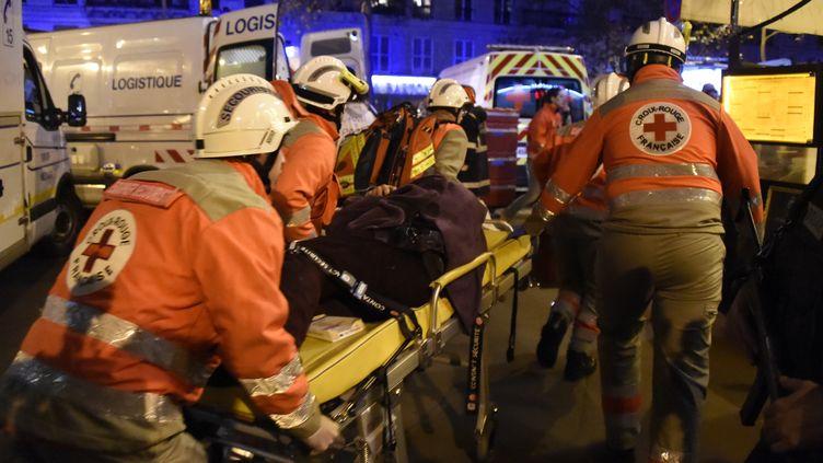 Des secouristes de la Croix-Rouge évacuent un blessé, le 13 novembre 2015, après l'attaque contre le Bataclan, dans le 11e arrondissement de Paris. (DOMINIQUE FAGET / AFP)