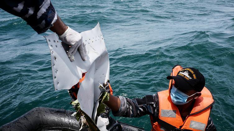 Des marins indonésiens repêchent, le 12 janvier 2021, un débris du Boeing de Sriwijaya Air disparu en mer trois jours plus tôt. (ANTON RAHARJO / ANADOLU AGENCY / AFP)