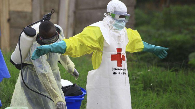 Un agent de santé asperge de désinfectant l'un de ses collègues dans un centre de traitementd'Ebola le 9 septembre 2018. (AL-HADJI KUDRA MALIRO/AP/SIPA / AP)