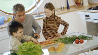 Une fille et un garçon cuisinent avec leur père. (MAXPPP)