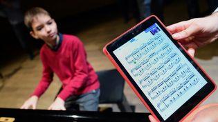 Un jeune pianiste interprète une partition affichée sur une tablette numérique. (ATTILA KISBENEDEK / AFP)