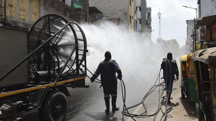 Des pompiers désinfectent les rues d'Ahmedabad(Inde), le 24 mars 2020. (SAM PANTHAKY / AFP)