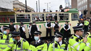 Des policiers entourent un véhicule garé en travers de la route, alors que des activistes climatiques du groupe Extinction Rebellion bloquent la route sur le London Bridge, dans le centre de Londres, le 31 août 2021. (JUSTIN TALLIS / AFP)