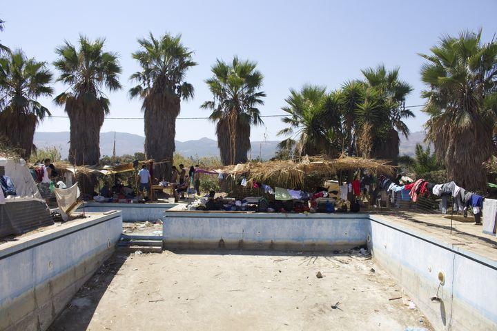 Des migrants campent autour de la piscine vide de l'hôtel Captain Elias transformé en centre d'hébergement, le 19 août 2015. (BENOIT ZAGDOUN / FRANCETV INFO)