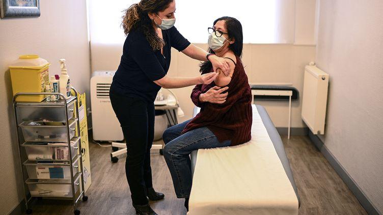 Un médecin administre une dose du vaccin AstraZeneca à une patiente, dans son cabinet médical, à Paris, le 25 février 2021. (CHRISTOPHE ARCHAMBAULT / AFP)