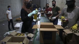 Des bénévoles libanais remplissent des cartons de nourriture pour aider les familles dans le besoinen pleine épidémie de coronavirus, le 29 mai 2020 à Beyrouth (photo d'illustration). (PATRICK BAZ / AFP)