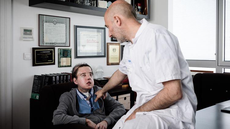 Jérôme Hamon, qui a reçu une greffe au visage, ci-contre avec l'un de ses médecins, le professeur Laurent Lantieri, à l'hôpital européen Georges Pompidou à Paris, le 13 avril 2018. (PHILIPPE LOPEZ / AFP)