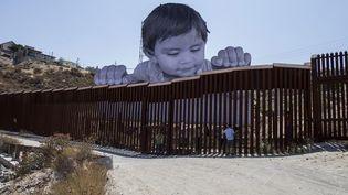 Cette photo géante de Kikito, un enfant mexicain,installée par l'artiste français JR, regarde par-dessus la barrière installée à la frontière des Etats-Unis (7 septembre 2017)  (Eduardo Jaramillo Castro / Notimex / AFP)