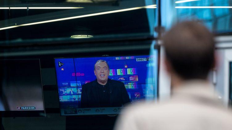 Un salarié de la chaîne i-Télé observe Jean-Marc Morandini animer le premier numéro de son émission, le17 octobre 2016 devant le siège du groupeCanal+ à Boulogne-Billancourt (Hauts-de-Seine). (MAXPPP)