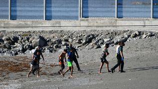 Des migrants en provenance du Maroc etdes gardes civils espagnols sur une plage de l'enclave espagnole de Ceuta, le 17 mai 2021. (ANTONIO SEMPERE / AFP)