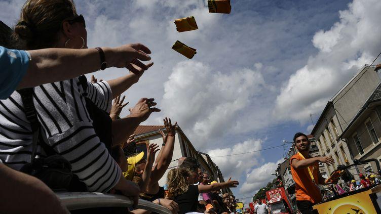 Les spectateurs du Tour de France reçoivent des goodies offerts lors du passage de la caravane, à Longwy (Meurthe-et-Moselle). (JEFF PACHOUD / AFP)