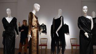 Des robes Yves Saint Laurent de Catherine Deneuve exposées à Christie's, sous l'œil d'une visiteuse intéressée (18 janvier 2019)  (Alain Jocard / AFP)