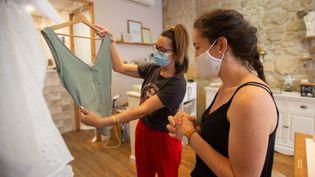 Une vendeuse et une cliente portent un masque dans une boutique de vêtements à Périgueux (Dordogne), le 18 juillet 2020. (ROMAIN LONGIERAS / HANS LUCAS / AFP)
