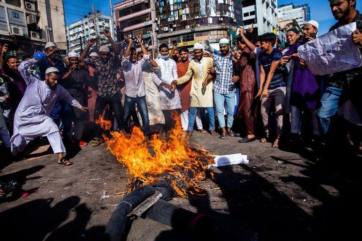 Des manifestants brûlent une effigie d'Emmanuel Macron lors d'une manifestation à Dacca (Bangladesh), le 30 octobre 2020. (MUSHFIQUL ALAM / NURPHOTO / AFP)