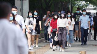 Des passants portent un masqueà Pékin, le 8 juin 2020. (KOKI KATAOKA / YOMIURI / AFP)