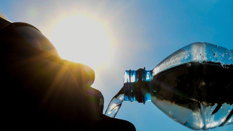 Un homme boit de l'eau à une bouteille, le 25 juillet 2018. (DENIS CHARLET / AFP)