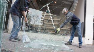 Des ouvriers remplacent la vitrine d'un concessionnaire brisée par des manifestants la veille, à Paris le 15 avril 2016. (MAXPPP)