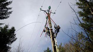 Des agents ERDF travaillent sur une ligne éléctrique dans l'Ouest de la France, en février 2014. (Photo d'illustration) (JEAN-SEBASTIEN EVRARD / AFP)