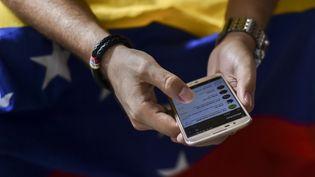 Un Vénézuelien utilise sont téléphone portable en Colombie, le 30 juillet 2017. (LUIS ROBAYO / AFP)