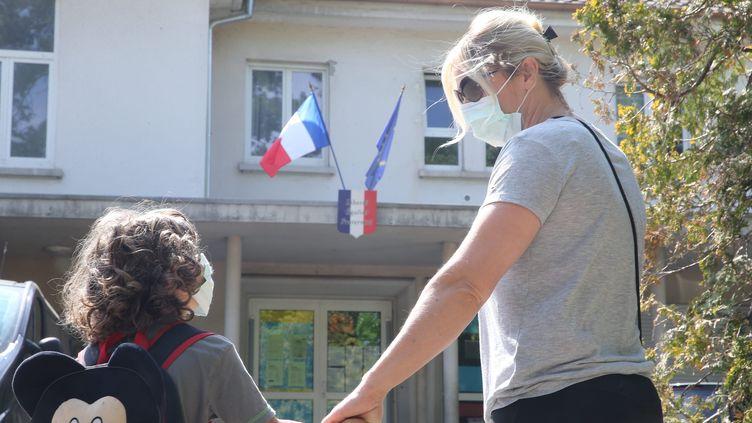 Un petit garçon et sa maman qui portent un masque devant une école. (photo d'illustration) (JEAN-FRANÇOIS FREY / MAXPPP)