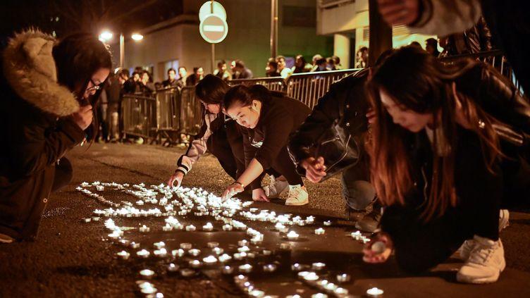 Des manifestants posent des bougies, dans le 19e arrondissement de Paris, après la mort d'un Chinois. (CHEN YICHEN / XINHUA / AFP)