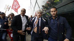 Pierre Plissonnier, le DRH de la division long-courrier d'Air France pris à partie, est escorté loin des manifestants en colère devant le siège de la compagnie, le 5 octobre 2015 à Roissy (Val-dOise). (KENZO TRIBOUILLARD / AFP)