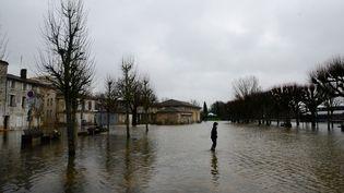 Un habitant de Saintes (Charente-Maritime) marche les pieds dans l'eau, le 6 février 2021.  (MEHDI FEDOUACH / AFP)