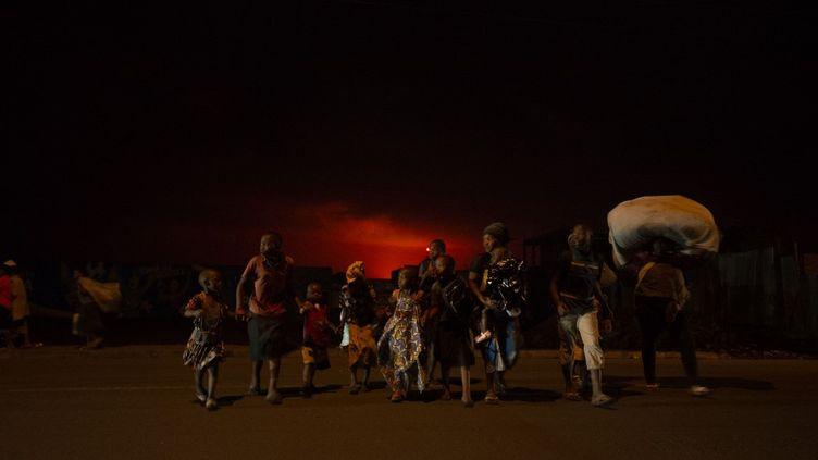 Des habitants de Goma fuient leur ville lors de l'éruption du volcanNyiragongo, dans la nuit du 23 mai 2021. (GUERCHOM NDEBO / AFP)
