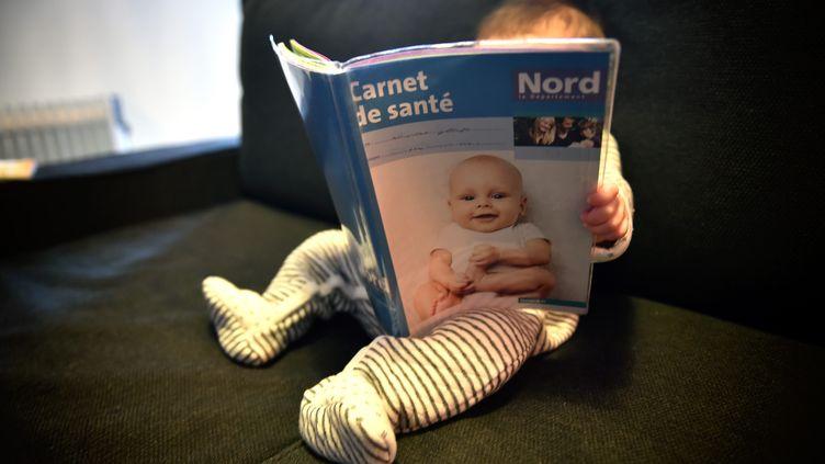 Un bébé feuilletant son carnet de santé à Valenciennes (Nord), le 2 janvier 2018. (MAXPPP)
