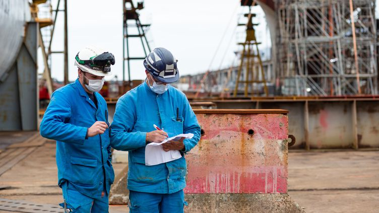 Deux travailleurs sur le site des Chantiers de l'Atlantique, le 8 octobre 2020 à Saint-Nazaire (Loire-Atlantique). (JEREMIE LUSSEAU / HANS LUCAS / AFP)