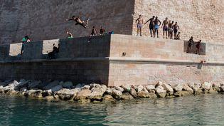 Des adolescents plongent dans le bassin du Fort Saint Jean à Marseille le 11 juillet 2017. (AURELIEN MORISSARD / MAXPPP)