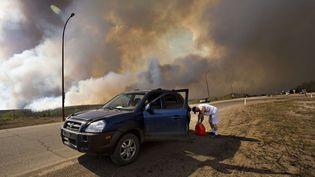 Un habitant de Fort McMurray (Canada) effectue une halte lors de l'évacuation de la ville, menacée par un gigantesque incendie, mercredi 4 mai 2016. (JASON FRANSON / AP / SIPA)