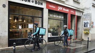 Deux livreurs de l'entreprise Deliveroo, à Paris, le 31 mars 2016. (ERIC FEFERBERG / AFP)