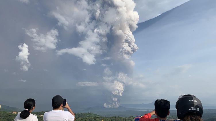 Des personnes prennent en photo l'éruption du volcan Taal, le 12 janvier 2020, près de Manille (Philippines). (BULLIT MARQUEZ / AFP)