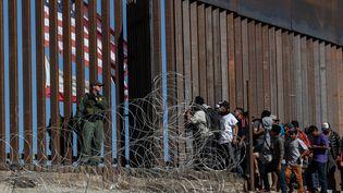 Des migrants en provenance d'Amérique centrale tentent de passer la frontière, le 25 novembre 2018, entre Tijuana (Mexique) et San Diego (Etats-Unis). (GUILLERMO ARIAS / AFP)