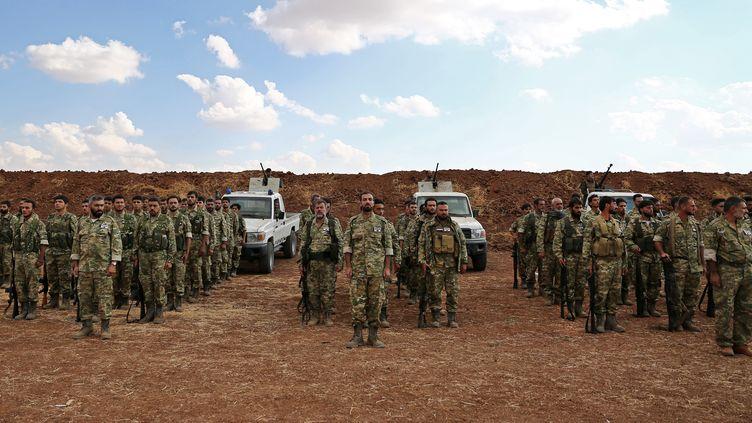 Des soldats syriens soutenus par la Turquie rassemblés près de la frontière turco-syrienne, au nord d'Alep, le 7 octobre 2019. (NAZEER AL-KHATIB / AFP)