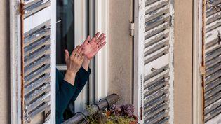 Une personne applaudit à la fenêtre d'un appartement, le 30 mars 2020, à Paris. (OMAR HAVANA / HANS LUCAS / AFP)