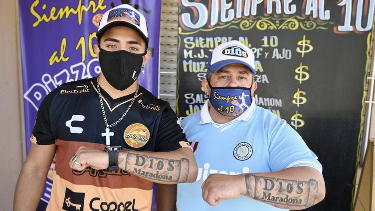 """Guillermo Rodriguezet son fils Axel, baptisés de l'église maradonienne, présentent le tatouage en l'honneur des 60 ans de Diego Maradona, et le """"Noël maradonien"""", le 29 octobre 2020. (JUAN MABROMATA / AFP)"""