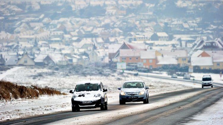 Des voitures couvertes de neige circulent sur une route près de Boulogne-sur-mer, dans le Pas-de-Calais, le 19 janvier 2013. (PHILIPPE HUGUEN / AFP)