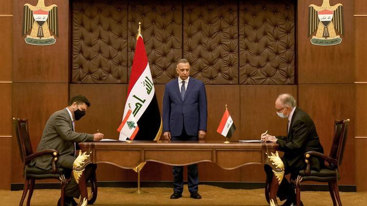 Le Premier ministre irakien Kadhemi (au centre) observe la signature de l'accord entre le Liban et l'Irak, le 24 juillet 2021. (IRAQI PRIME MINISTER'S PRESS OFFICE / AFP)