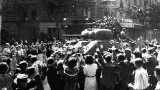 25 août 1944, des Parisiens acclament des chars de la 2e Division blindée du général Leclerc entrant dans Paris. (COLL-DITE/USIS / AFP)